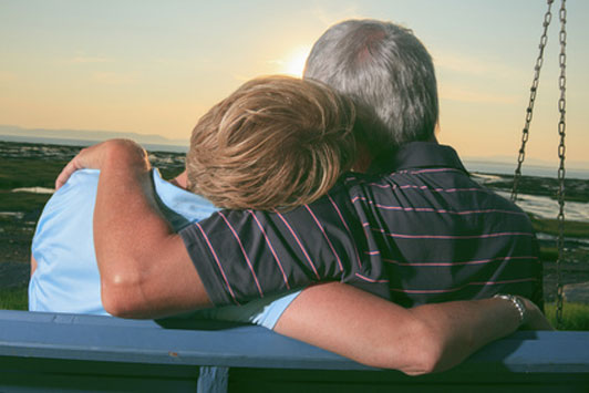 couple with age gap on bench watching sunset