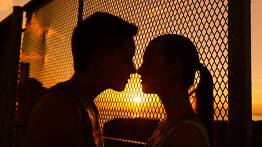 two people about to kiss in front of fence