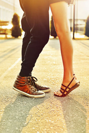 couple with feet facing each other and woman on tip toes