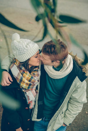 warmly dressed couple kissing near leaves