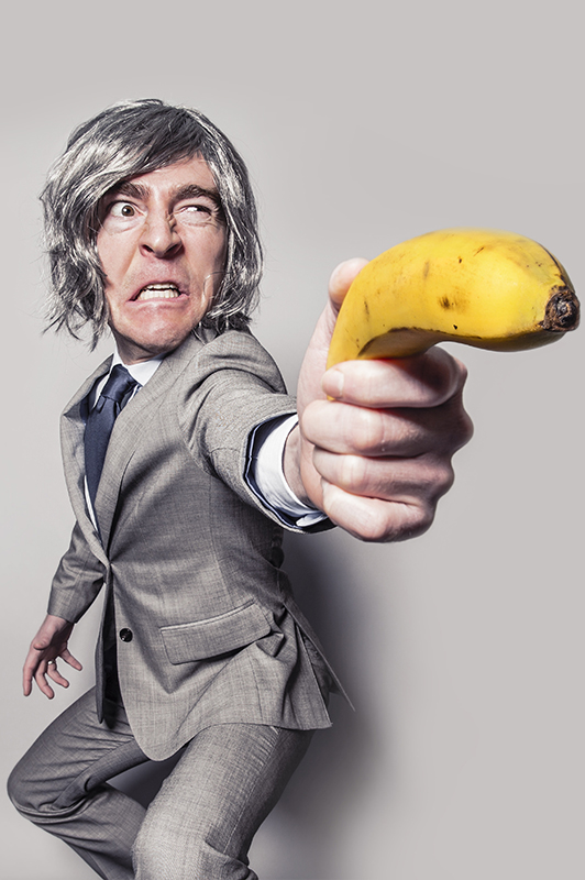 A guy with silver wig holding a banana.