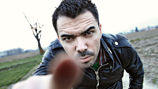 A guy with a frowny face pointing with his finger.