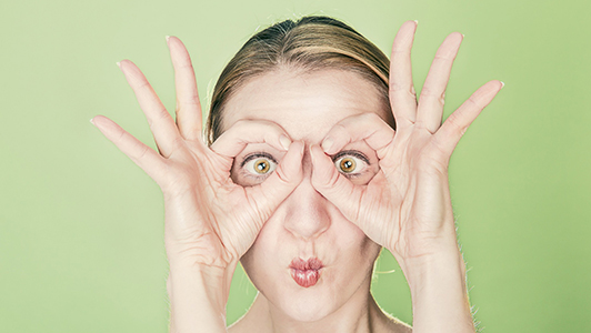 Woman making funny faces and holding her hands shaped like glasses.
