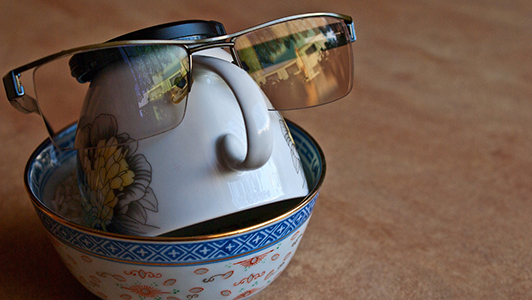 A bowl, a cup, and glasses shaping a head.