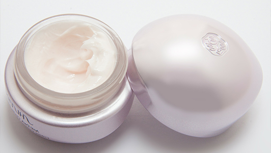 An opened white package of a face cream.