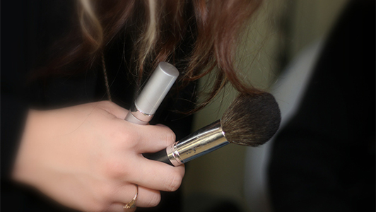 Girl holding a makeup brush and lipstick.