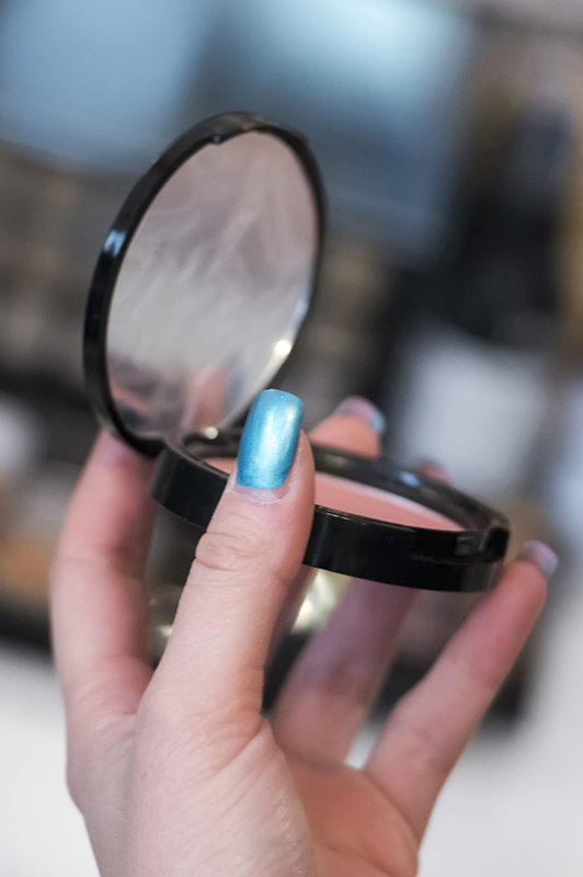 Girl with blue nails holding pressed powder.