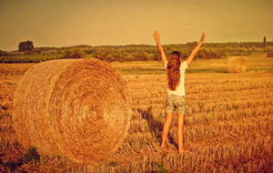 barefoot woman in open field standing next to hay with arms lifted up high