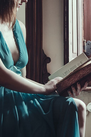 woman in green dress with open book