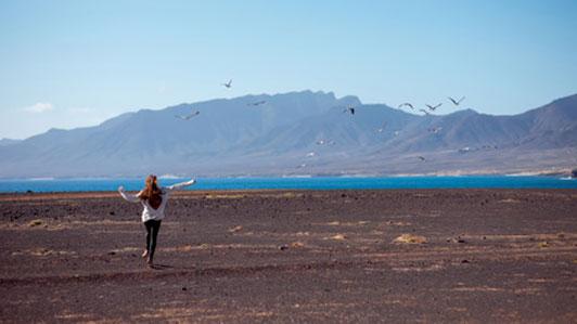 woman in good mood running forward towards beach