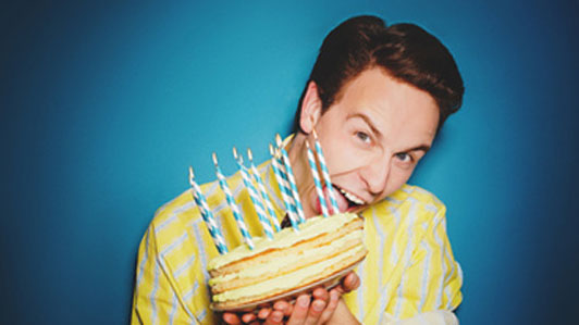 guy gnawing at cake with candles