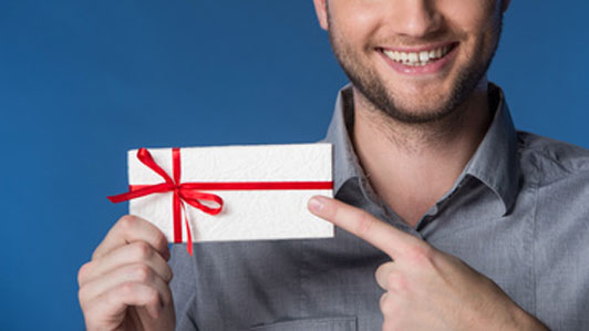 smiling man pointing at gift card