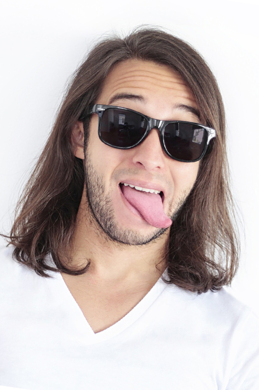 A guy with long hair sticking his tongue out.