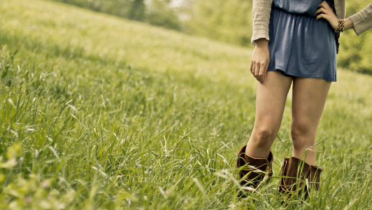 Girl in short dress standing in the meadow.