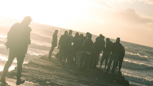 A group of people looking at sea.