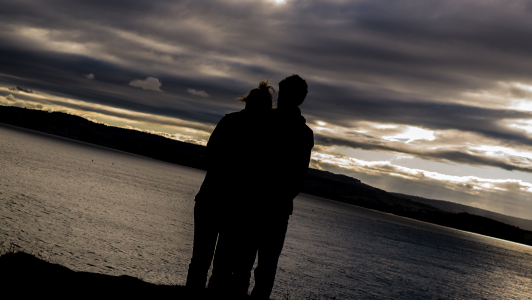 Couple standing near a lake.