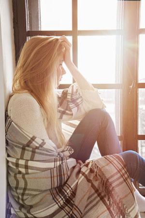 woman sitting alone near window thinking
