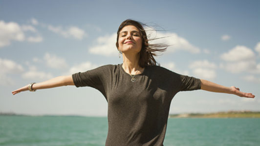 women with arms wide open closing eyes while breathing fresh air