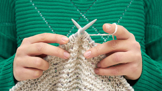 woman in green sweater kniting