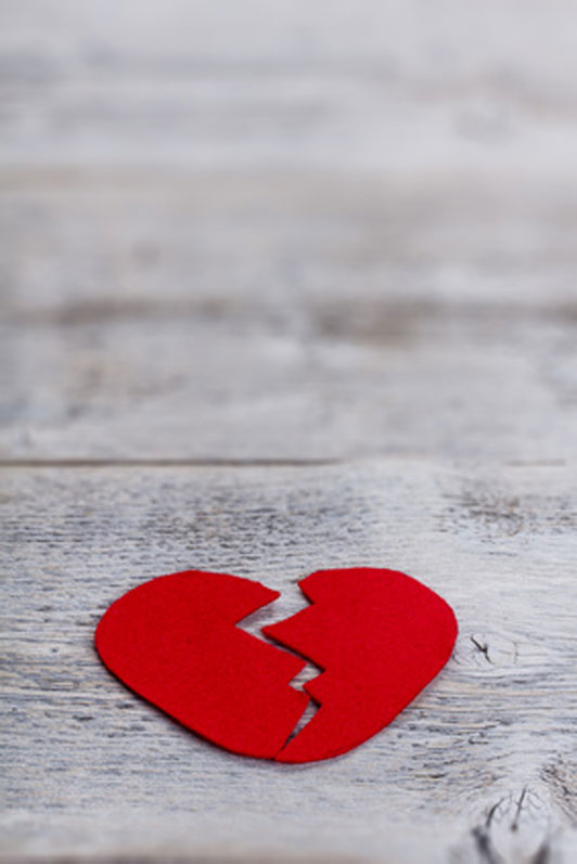 red broken heart on wooden surface