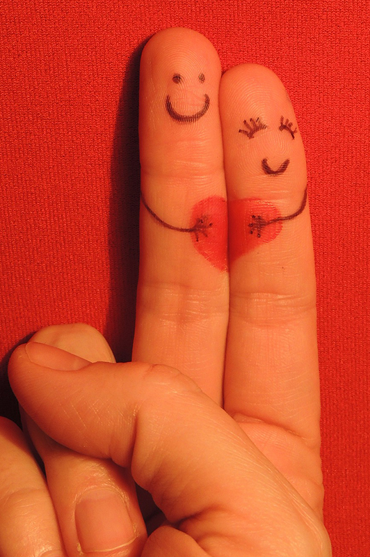 Two hearts with smiley faces and a heart drawn on them