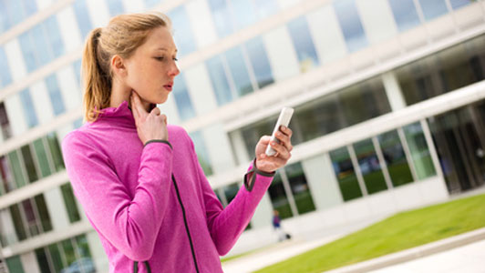 woman looking at phone checking heart rate