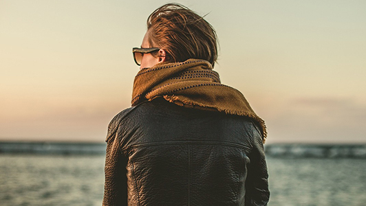Back of a girl in a leather jacket wearing sunglasses.