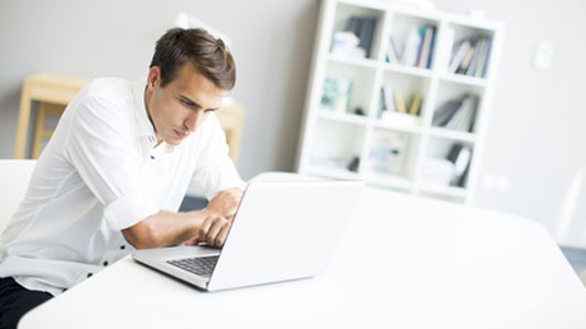 determined looking man working on laptop