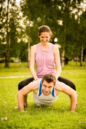 woman sitting on the back of a man while he does pushups