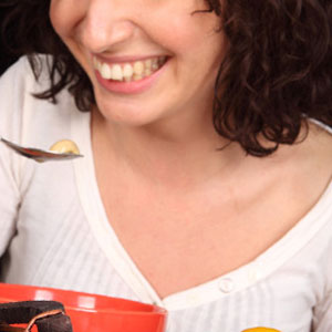 woman spooning food into face in front of dark background