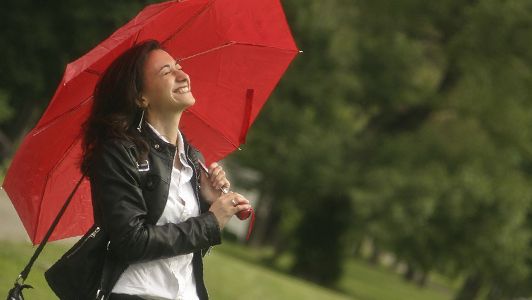 A girl with a wide grin carrying an umbrella.