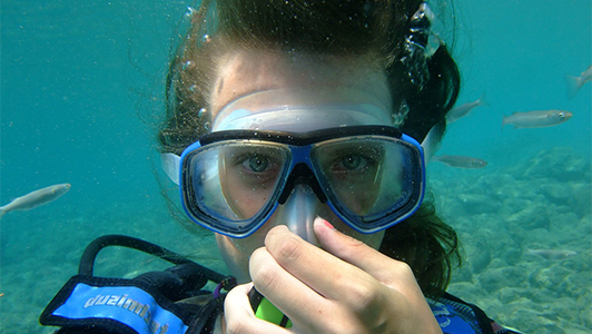 Girl carrying a mask under water