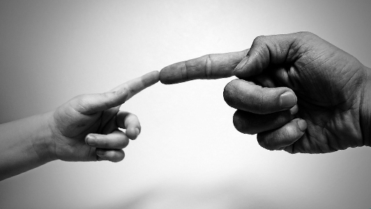 A finger of a child touching a finger of a grown man