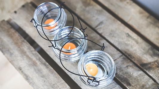 Three tea light candles in glass jars