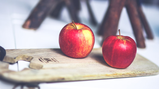 Two apples on a cutting board