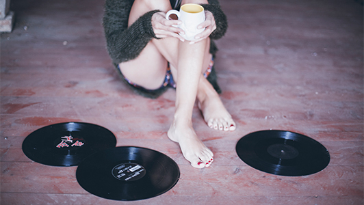 girl sitting surrounded with vinyls