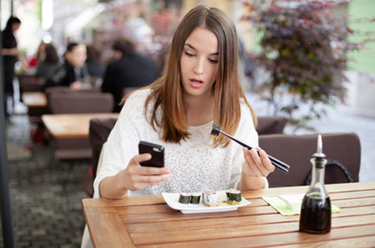 woman texting while eating sushi