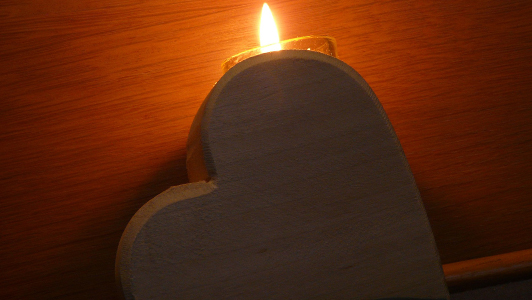 wooden heart holding a candle