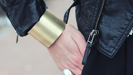 Close-up of an outfit including leather jacket and a golden bracelet