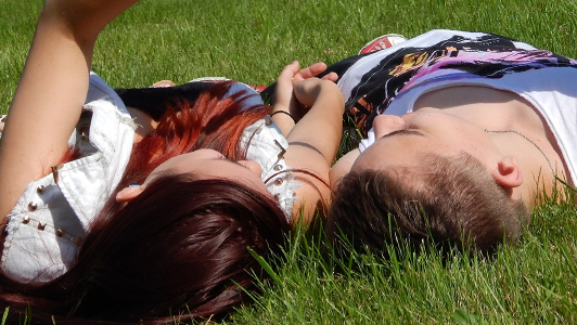 A couple lying on grass.