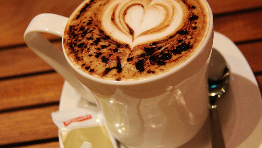 A cup of coffee with heart shapes in the foam.
