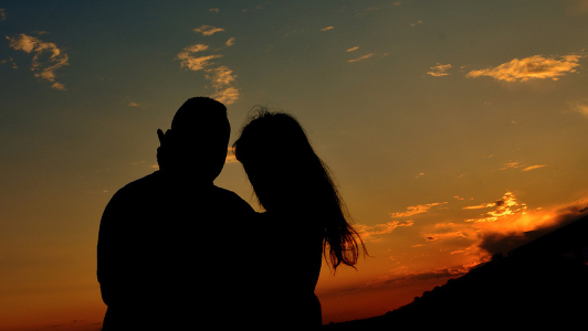 Silouette of a couple standing in the sunset