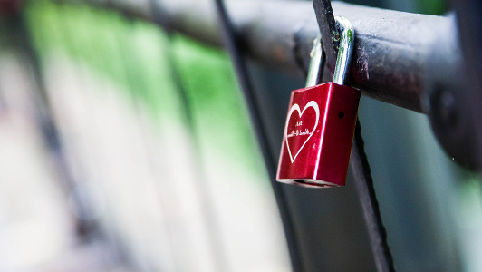 Red padlock with white heart attached to a gate.