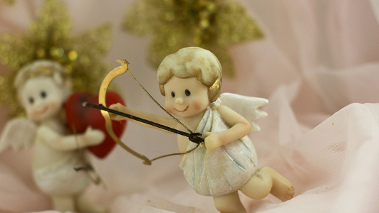 Little Cupid holding bow and arrow.