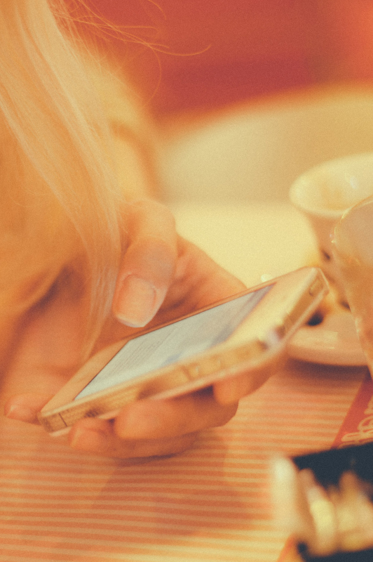 Girl with blonde hair texting.