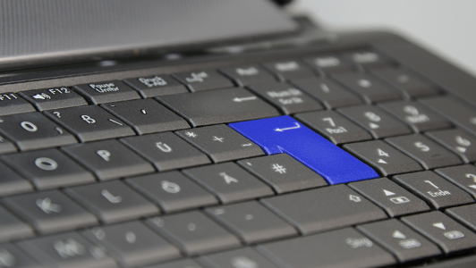 Laptop keyboard with a blue enter button.