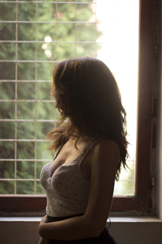 Girl in a white top looking through a window.
