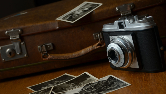 Old suitcase, camera and black and white photos.