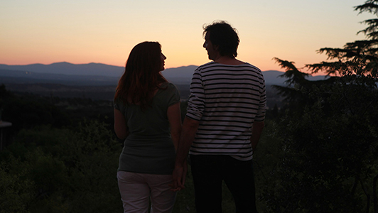 Couple holding hands and looking at each other in sunset.