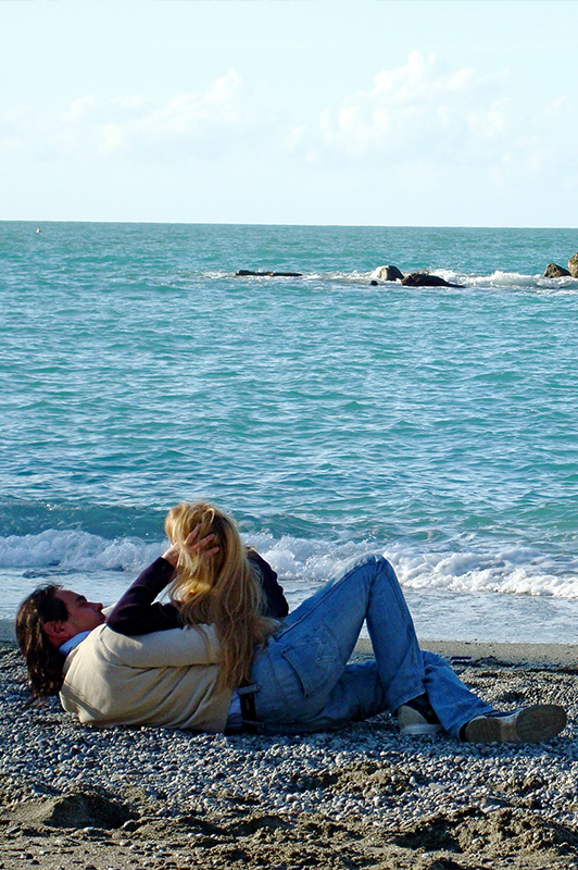 Man in jeans and sweater lying on a beach with a blonde girl.